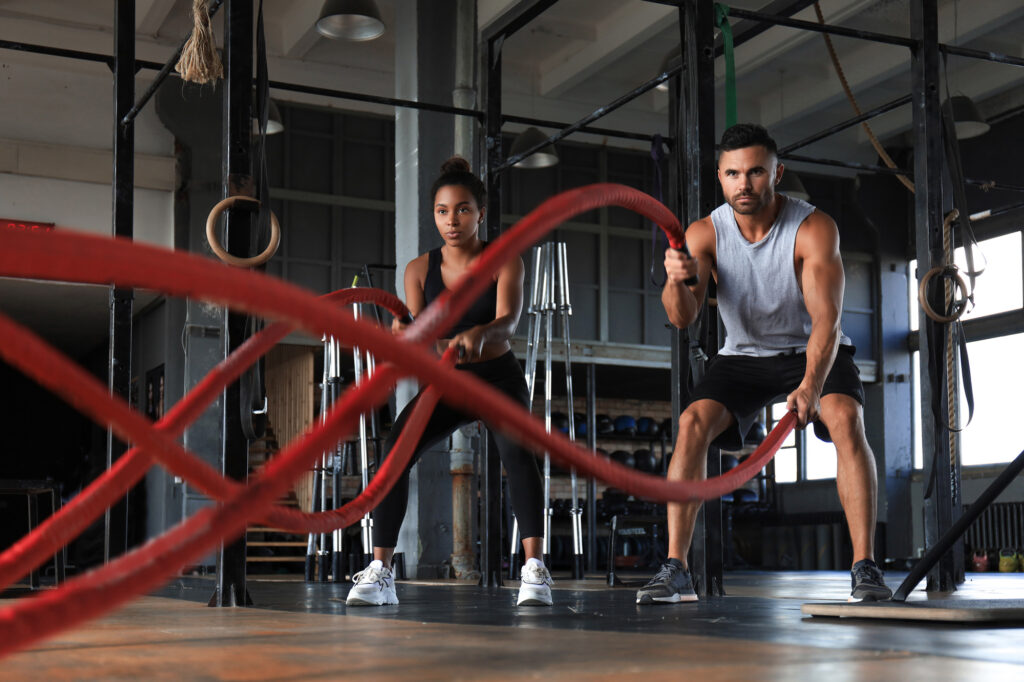 Athletic young couple with battle rope doing exercise in functional training fitness gym