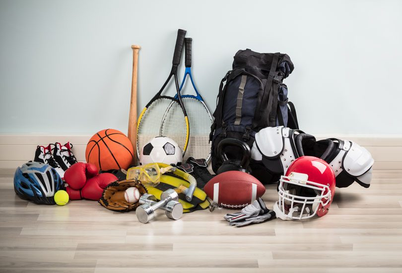 Different Type Of Sports Equipment On Wooden Desk Against White Wall